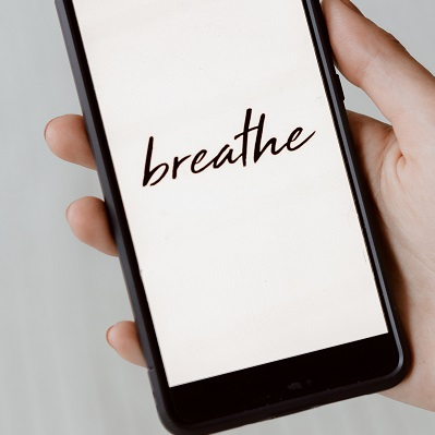 Image of a person's hand holding a smart phone with the word breath written on the screen. Captioned: What's the Latest on Covid Mortgage Relief?