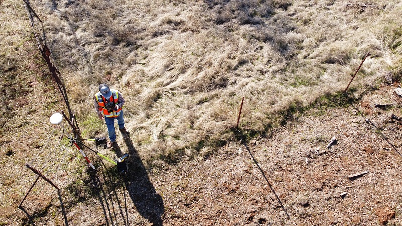 Image of a surveyor inspecting property line on a piece of real estate outside.