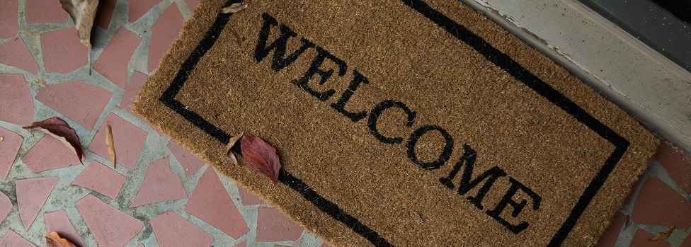 Close up image of a welcome mat on a house doorstep. Captioned: Race Restrictions Still Appear on Deeds. There's a Movement Afoot to Delete Them.