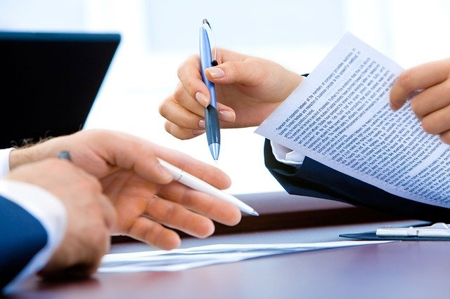 Image of people reviewing legal documents on a table with pens in hand. Captioned: Fine-Tuning Your Mortgage: Can a Recast Loan Make Sense?