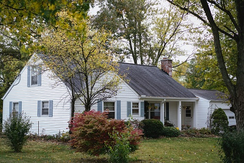 Image of the outside of a house in a wooded setting, Captioned: Top 5 Reasons for Using a Quitclaim Deed.