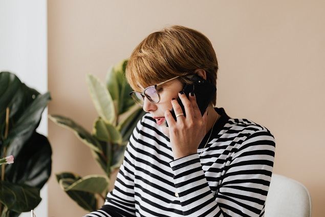 A person on the phone falling for a real estate closing scam.