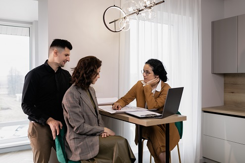 Three people gathering at a table to discuss a contingent real estate offer.