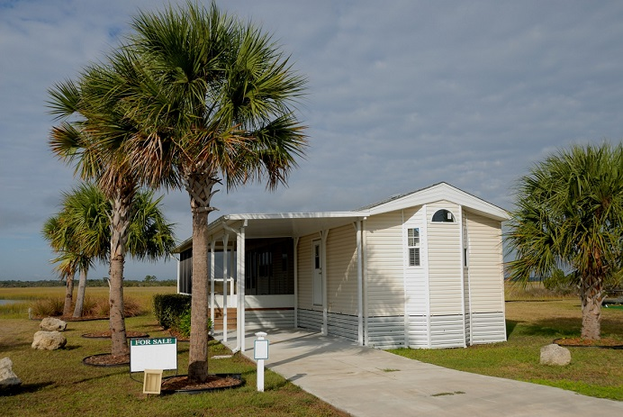 Mobile home exterior with a driveway and palm trees. Captioned: Convert a Mobile Home Title to a Real Estate Title
