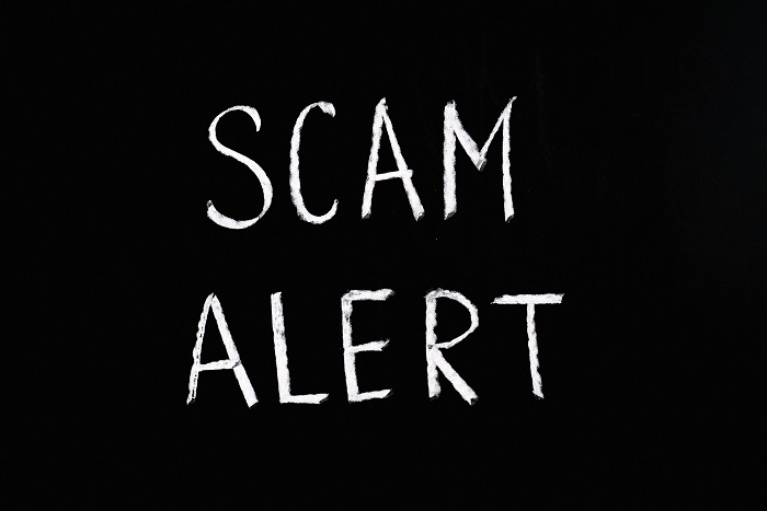 """Image of the words """"Scam Alert"""" in white in a black background."""