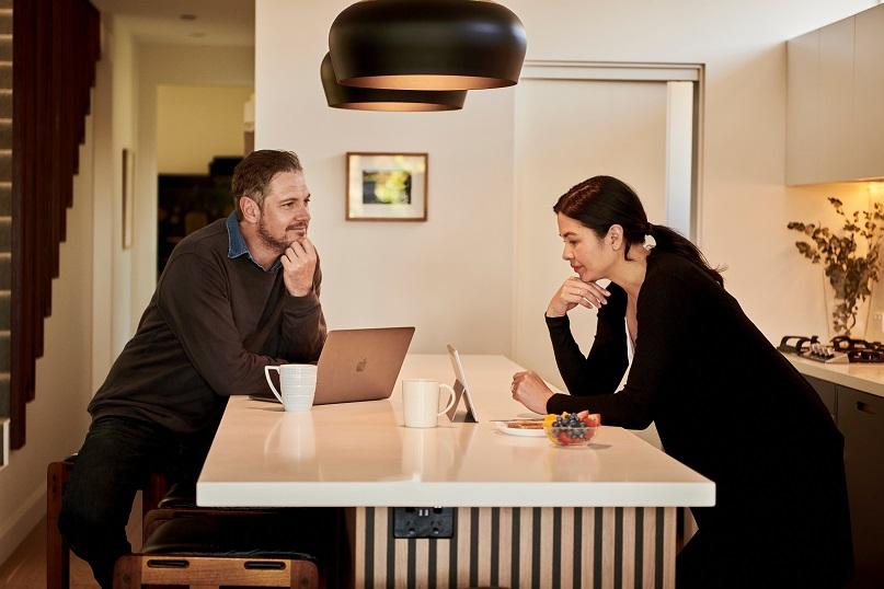Image of two people leaning on a table looking at computers. Captioned: Notaries Go Remote: A Digital Shift Is Changing Notary Language