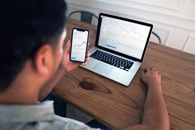 Person looking at a cell phone and a computer while sitting at a desk. Captioned: The Rise of the Outside-the-Box Mortgage Applicant