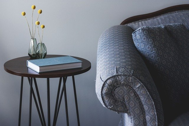 Image of a chair and end table with a book and small flowers.