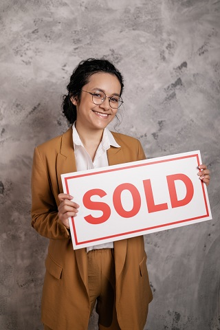 Image of a person holding a sold sign.