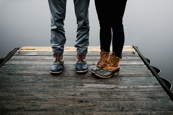 Image of the legs of two people standing on a dock near a body of water.