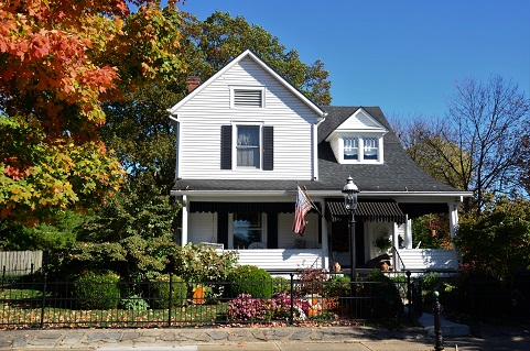 Image of the outside of a house, lots of mature landscaping, likely during the fall as the leaves are changing colors.
