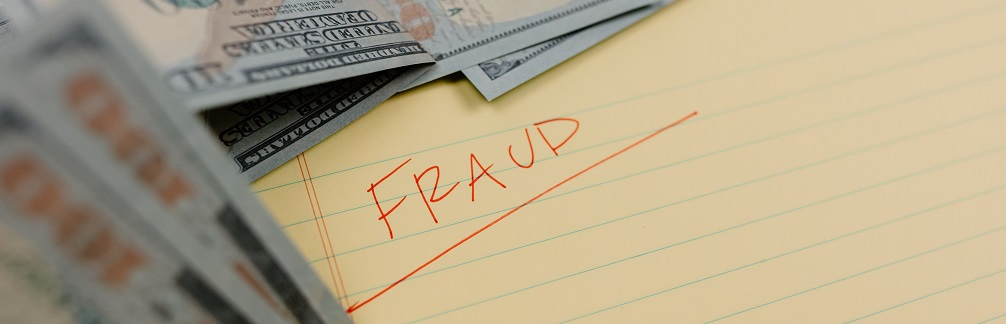 """The word """"Fraud"""" written in red ink on a piece of legal paper surrounded by some U.S. paper currency. Captioned: Closing Scams Now Make Up Nearly Half of Cybercrime Losses"""