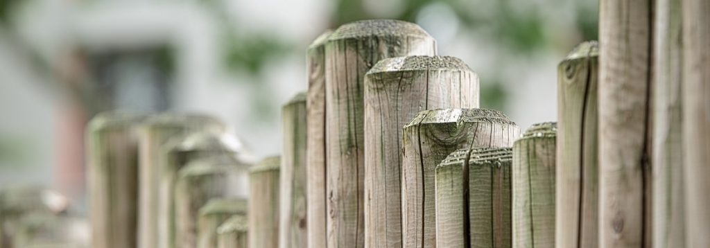 Image of the top of an uneven post fence line. Captioned: Resolving a Property line Dispute in 5 Steps