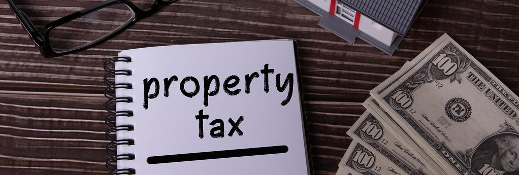 """Image of a notebook sitting on a table with the words """"property tax"""" written in it."""