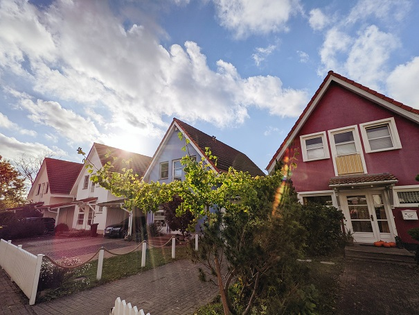 Image of a row of houses backlit by the sun with fluffy clouds in a mostly blue sky. Captioned: The Rise of the Property Tax Protests