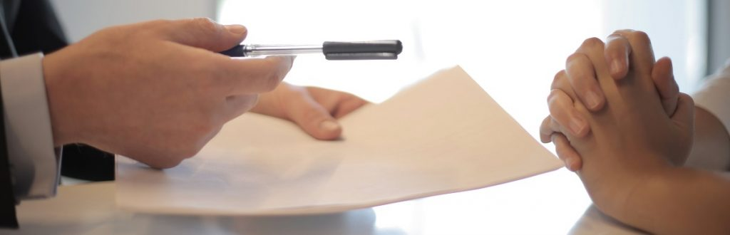 Image of legal documents being offered for signature from one person to another person seated at a table. Captioned: Selling Your Home? A Few Things to Know About Listing Agreements