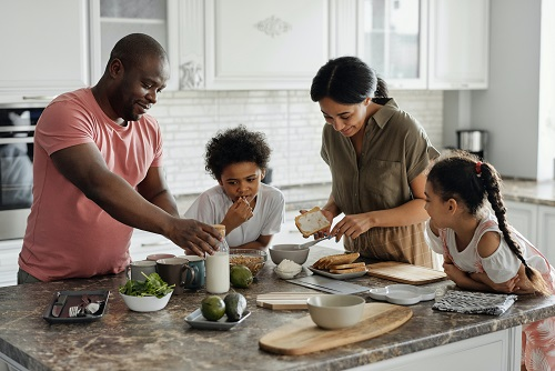 Happy family gathered in a kitchen preparing food. Captioned: Administration Confronts Racial Bias in Appraisals