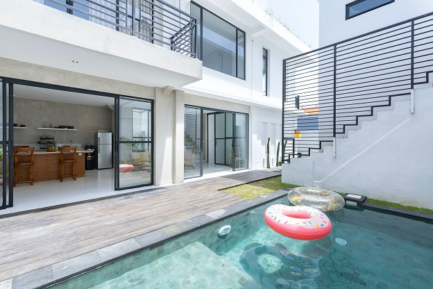 Image of a pool area surrounded by living area of a condo or house.