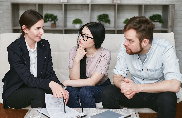 Image of three people sitting on a couch in a house discussing how to take someone of a home mortgage obligation.