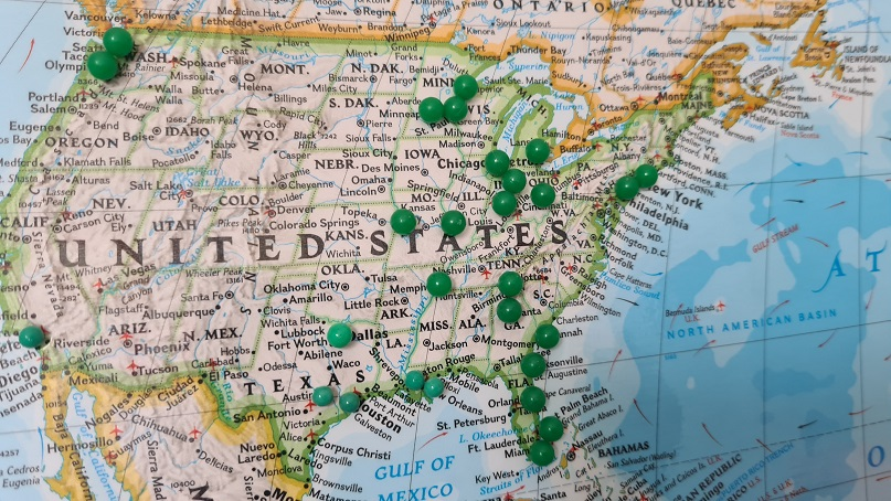 Image of a map of the United States with green pushpins marking locations of foreign real estate investing.