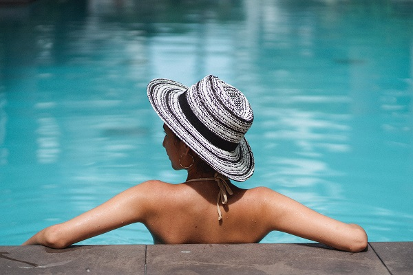 A person relaxing in a pool. Captioned: Do I Understand the HOA Tradeoff?