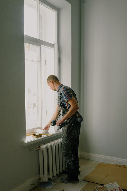 Image of a person working on house windows in an old house.