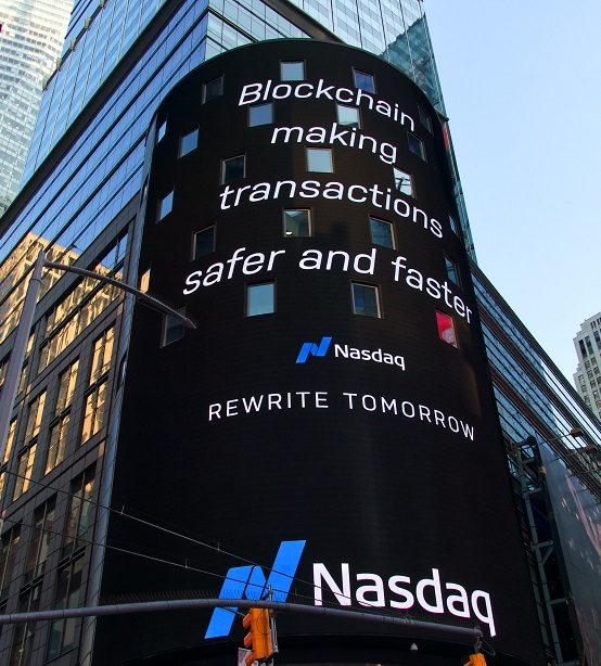 Image of the Nasdaq billboard with a city scape in the background. Captioned:  Blockchain in Payments and Real Estate Transactions.