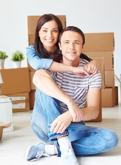 Two people sitting in a house with moving boxes behind them,
