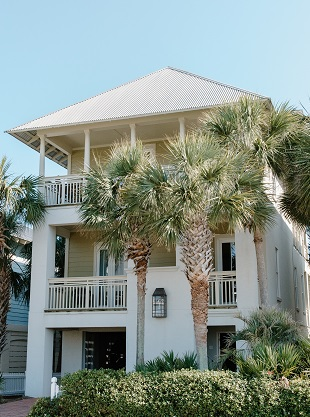 Image of a tall house with palm trees in front.