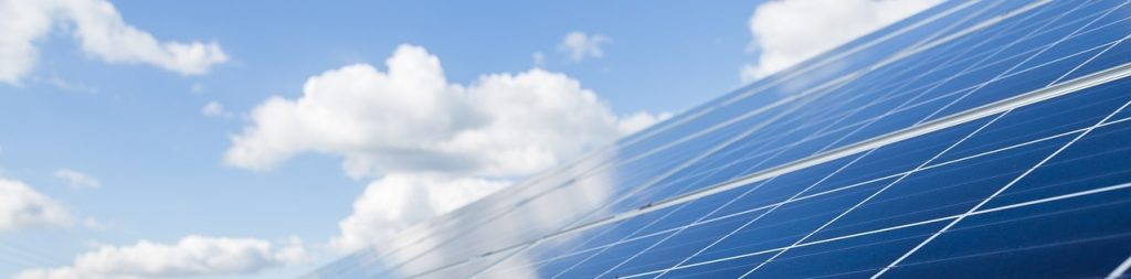 Image of solar panels facing a bright blue sky with some fluffy white clouds floating by.