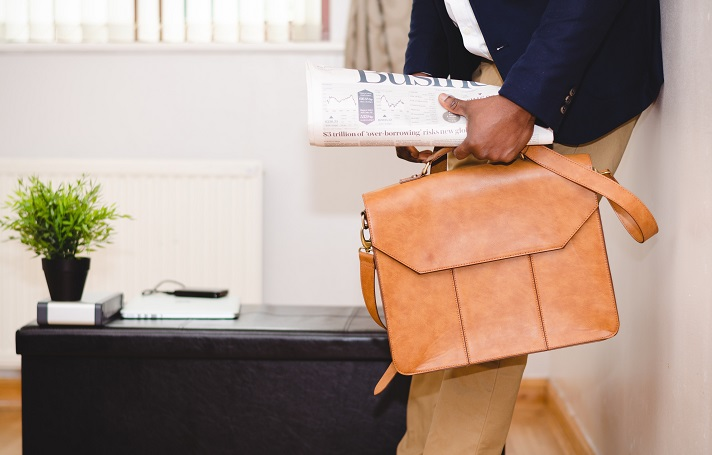 Person walking into a house carrying a newspaper and a soft briefcase.