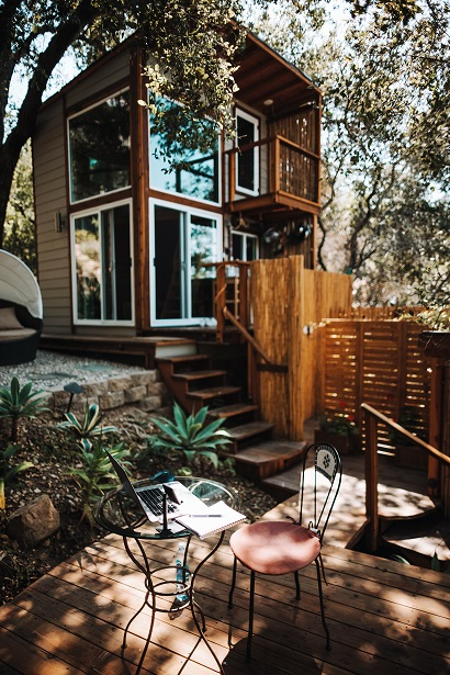 Image of a very nice tiny home with a patio and landscaping.