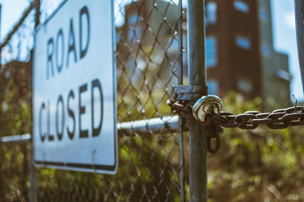 Image of a locked gate with a road closed sign on it.