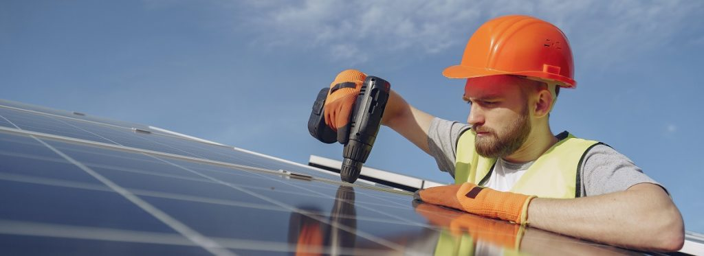 Person working on solar panels on top of a house.