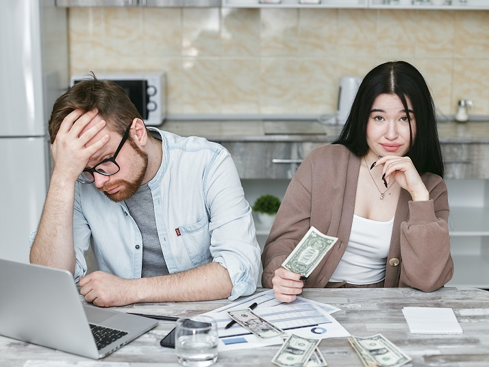 Two people sitting at a table looking stressed over money