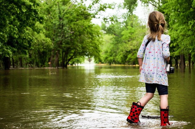 A young person in rain boots walking in shallow water.