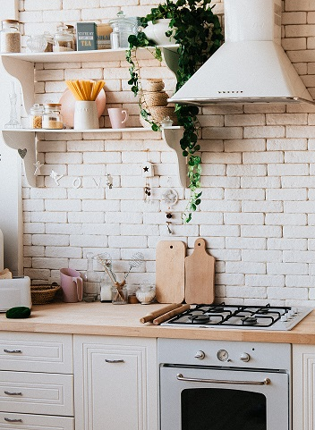 Close image of the kitchen area of a house showing a stove, oven, counter, and some cabinets and shelves. A nice exposed brick wall in the background.