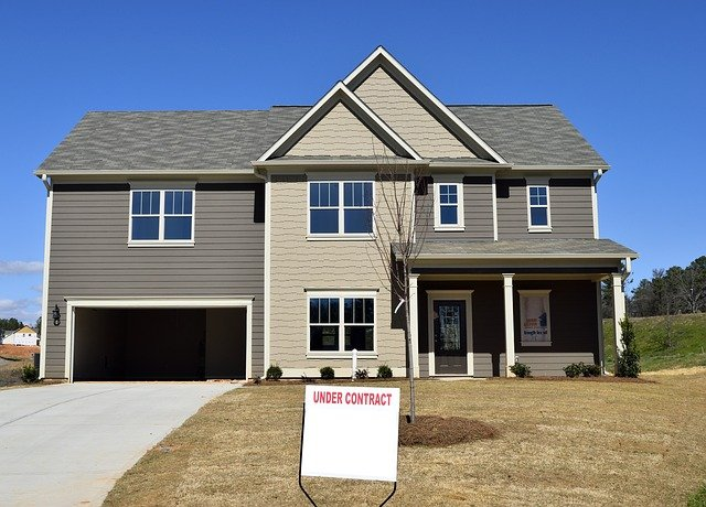 """Image of a house with a sign in front that reads: """"Under Contract"""""""