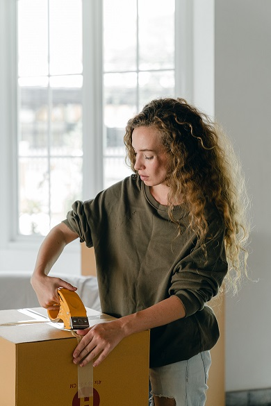 A person taping up a moving box.