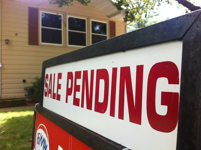 """Image of a """"sale Pending"""" sign in front of a house."""